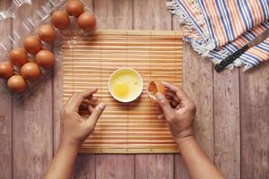 Man breaking egg and pouring into a small container on table photo