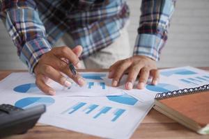 Mano de hombre con lápiz analizando gráfico de barras en papel y sosteniendo un teléfono inteligente foto