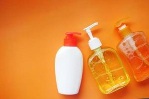 Líquido de lavado a mano en un recipiente sobre fondo naranja foto
