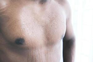 Young man skin sweating in chests photo