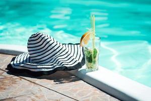 cóctel alcohólico de frutas a base de lima, menta, naranja, refresco de pie en el borde de la piscina foto