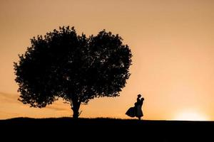 silhouettes of a happy young couple guy and girl on a background of orange sunset photo