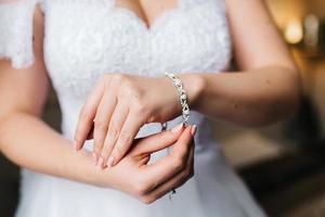 the bride wears a wedding bracelet on her left hand photo