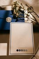 wedding invitation in a gray envelope on a table with green sprigs photo