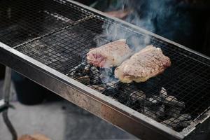 Asa la carne en la parrilla de carbón para cocinar bistecs foto