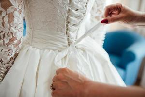 dress up the bride in a wedding dress with corset and lacing photo