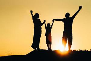 silhouettes of a happy young happy family against an orange sunset photo