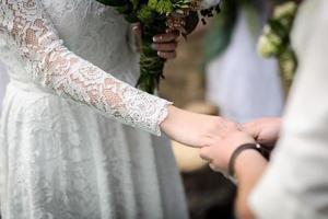 groom puts wedding ring photo