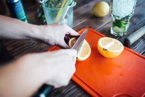barman prepara cóctel de alcohol de frutas a base de limón, menta, naranja, soda foto