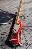 La guitarra eléctrica roja en un soporte está en el suelo. foto