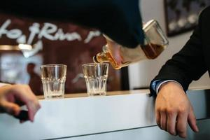two guys at the bar drink whiskey from crystal glasses photo