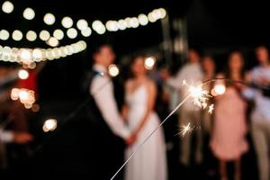 sparklers at the wedding, a couple of newlyweds on the background photo