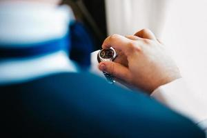 the groom in a blue suit looks at the watch worn on his left hand photo
