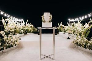 pastel de boda blanco en un soporte alto cerca del podio blanco foto
