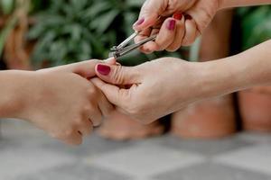 La mano de la mujer está usando un cortaúñas para cortar las uñas de un niño. foto