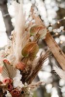 Área de ceremonia de boda con flores secas en un prado en un bosque de pinos foto