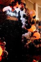 una zona de fotos temática de ángeles y demonios en negro con bolas blancas y negras