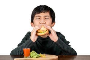 lindo chico asiático en camisa negra comiendo una deliciosa hamburguesa foto