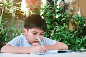 chico asiático haciendo sus deberes foto