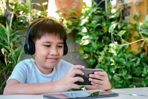 Chico asiático usando audífonos sonriendo y jugando en su teléfono inteligente. foto