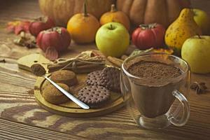 Hot cocoa, cookies and autumn harvest on wooden table. photo