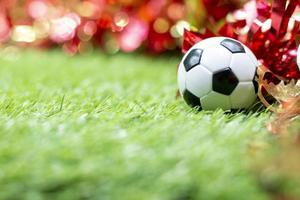 Soccer ball with Christmas decoration on green grass photo