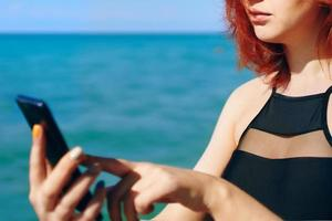 Red-haired woman writes message on her mobile phone photo