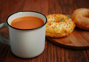 Cup of pumpkin juice and two sweet doughnuts with lemon glaze. photo
