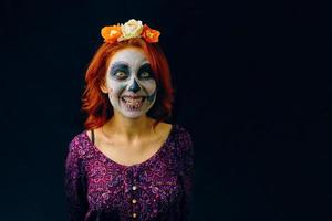 A young woman in day of the dead mask skull face art. photo