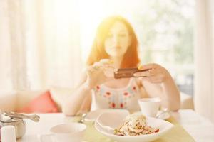 Red-haired woman takes photos of salad on smartphone camera.
