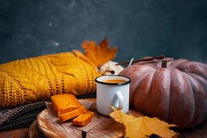 Juice, carrot cake on wooden stand, knitted sweater, pumpkin and leaves. photo