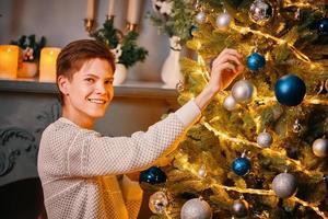 Smiling guy decorating Christmas tree. photo