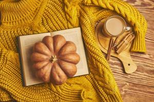 cálido suéter acogedor, libro abierto y calabaza sobre fondo de madera. foto