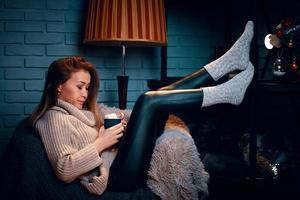 Serious girl in sweater on chair. photo