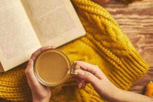 taza de café, chaqueta de punto acogedora y libro abierto sobre tabla de madera. foto