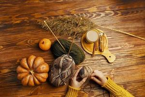 Women's hands with ball of yarn, pumpkin, coffee on wooden background. photo