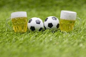 Balón de fútbol y vaso de cerveza en la hierba verde foto