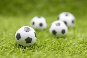 balones de fútbol están sobre fondo de hierba verde foto