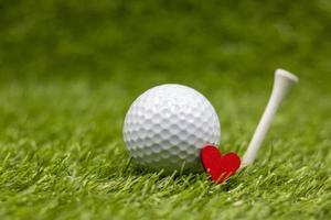 Golf ball with tee is on green grass with love photo