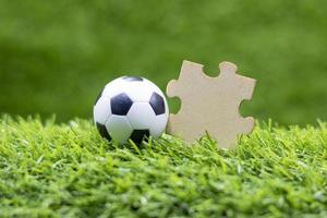 Balón de fútbol con rompecabezas está sobre la hierba verde foto