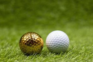 Golden golf ball with white golf ball are on green grass photo