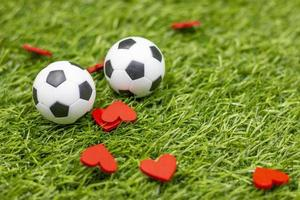 Soccer ball with red heart are on green grass photo