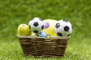 Soccer ball with Easter Holiday Decoration on green grass background photo