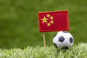 Balón de fútbol y la bandera de China están sobre fondo de hierba verde foto
