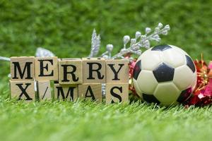 Soccer ball with  Merry Christmas wooden block are on green grass photo