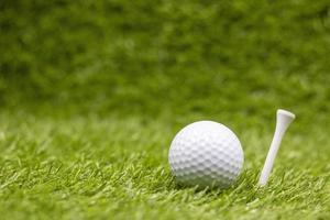 Golf ball with tee are on green grass photo