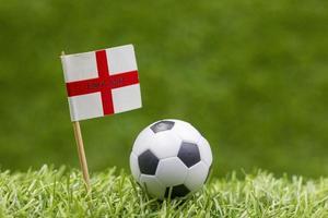 Balón de fútbol con la bandera de Inglaterra sobre la hierba verde foto