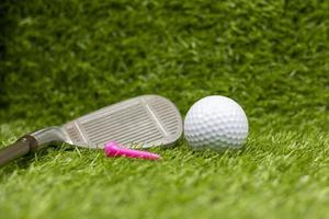 Golf ball with tee and iron are on green grass photo