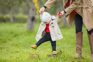 Cute funny happy baby making his first steps on a green lawn in autumn garden, mother holding his hands supporting by learning to walk photo