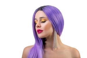 Retrato de una hermosa joven con un elegante maquillaje brillante y una peluca violeta aislado sobre fondo blanco. foto